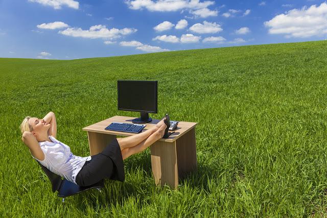 Photo d'une femme rêvant dans son bureau d'une prairie verte.