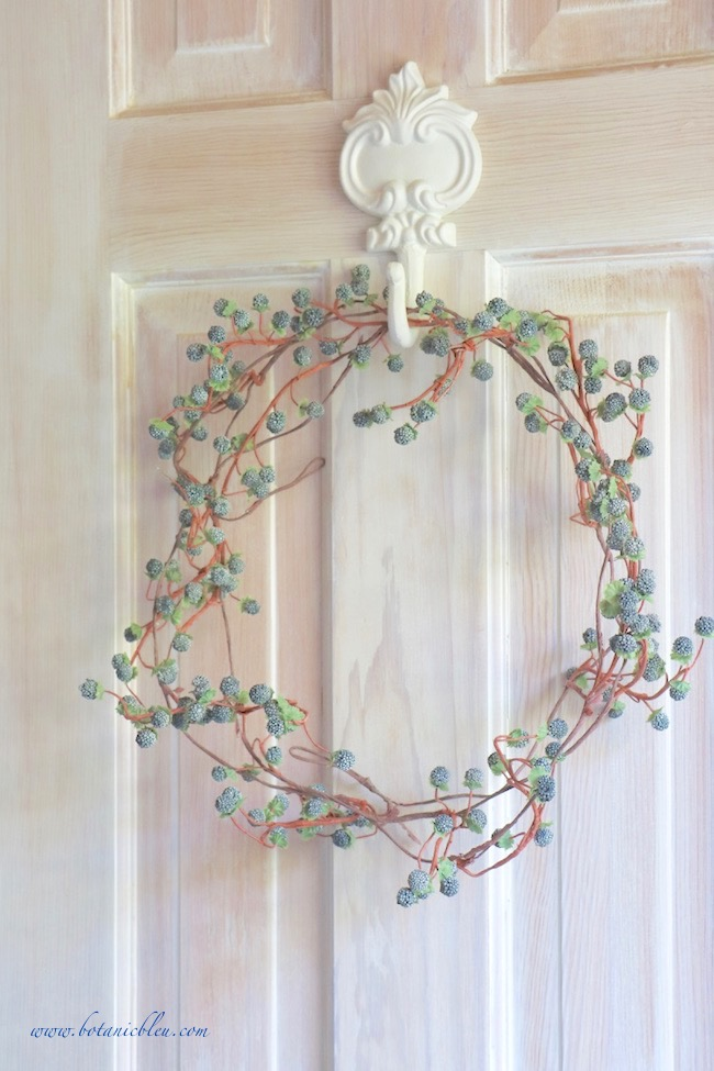 a simple berry wreath adds French Country style to a bathroom door