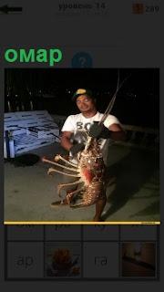 На берегу в вечернее время рыбак демонстрирует пойманного омара