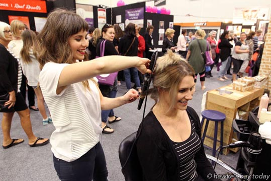 L-R: Kathryn Farnworth, The Good Place, Ahuriri, Napier, $15 hairdo for Jessica Clark, Havelock North - Women doing what women love doing at the Women's Lifestyle Expo at the Pettigrew.Green Arena in Taradale, run by NZME Events. photograph