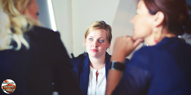 """Featured in the article: """"7 Tips To Help You Transitioning From Peer To Manager"""". Represents a businesswoman, now manager, listening to former peers feeback, now employees."""