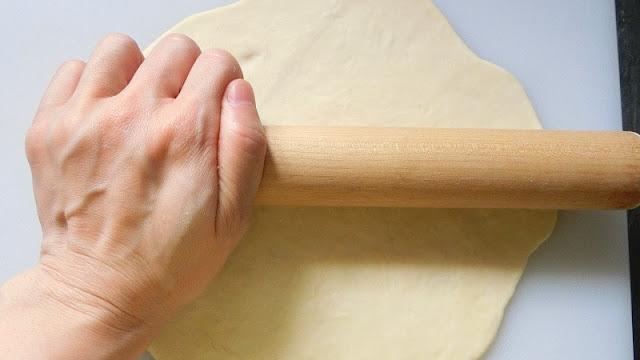 ピザ生地を麺棒で伸ばす