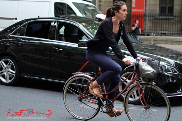 woman cycling in wedge sandals blue pants and cardigan, white music ear buds. Paris photos by Kent Johnson for Street Fashion Sydney.