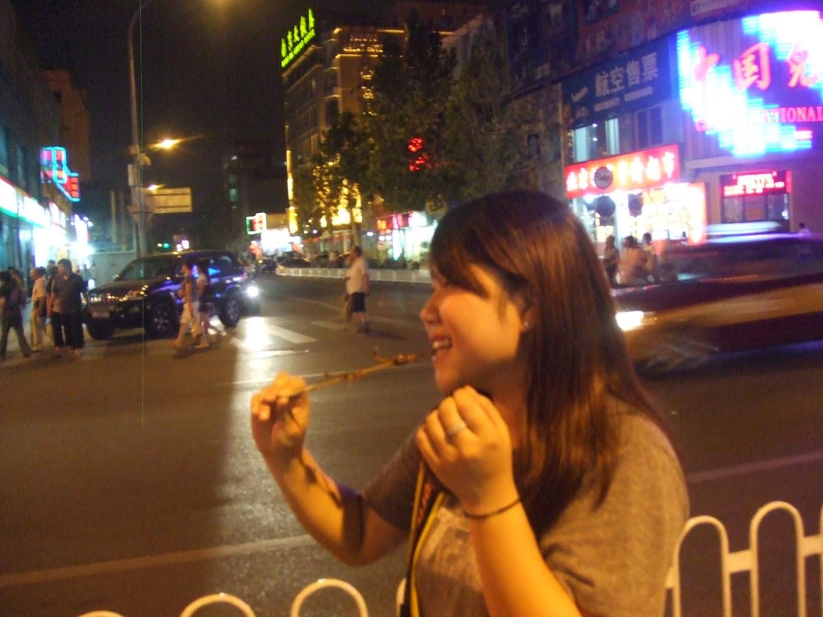 Chinesin isst Spinnentier in der Stadt am Abend