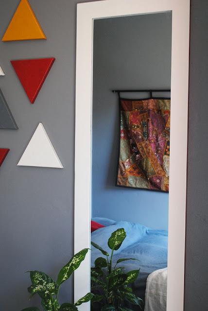 Spiegel in de slaapkamer met de reflectie van de wall hanging, naast kleine schilderijtjes en een Dieffenbachia.