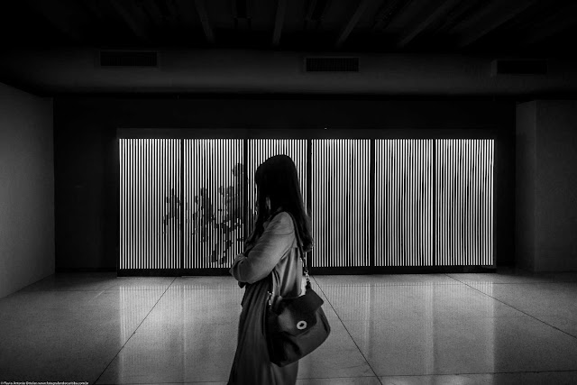 Foto em preto-e-branco de senhora no interior do Museu Oscar Niemeyer