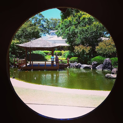 Pond in a Japanese garden with pagoda next to it, seen through a round window.