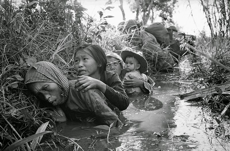 Women and children crouch in a muddy canal as they take cover from intense viet cong fire at bao trai about 20 miles west of saigon on january 1 1966