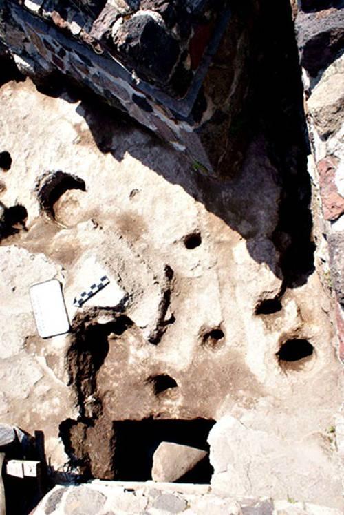 Algunas de las oquedades en el tepetate y una de las fosas con estela verde en el flanco sur de la Estructura A.