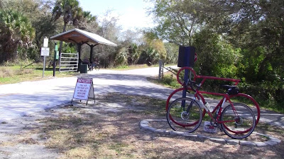 Bicylce trail with path to neighborhood and sculpture of bicycle