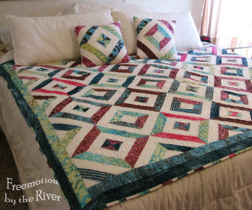 Petunia Strings by the River quilt and pillows on the bed