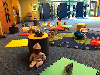 Program room with toys, books, colorful rugs, and squares