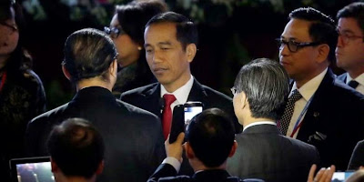 Para delegasi menggunakan smartphone, berebut selfie dengan Presiden Joko Widodo (Jokowi), usai menyampaikan pidato di acara APEC CEO Summit di China National Convention Center di Beijing, 10 November 2014.