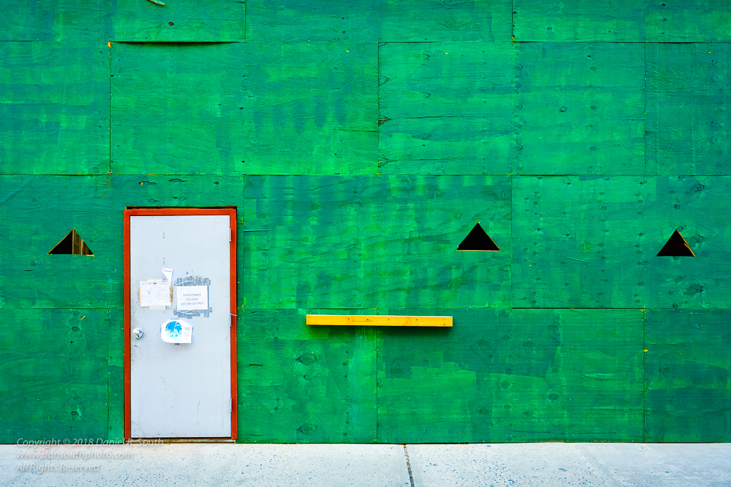 a photo of a green plywood construction wall in midtown manhattan new york city