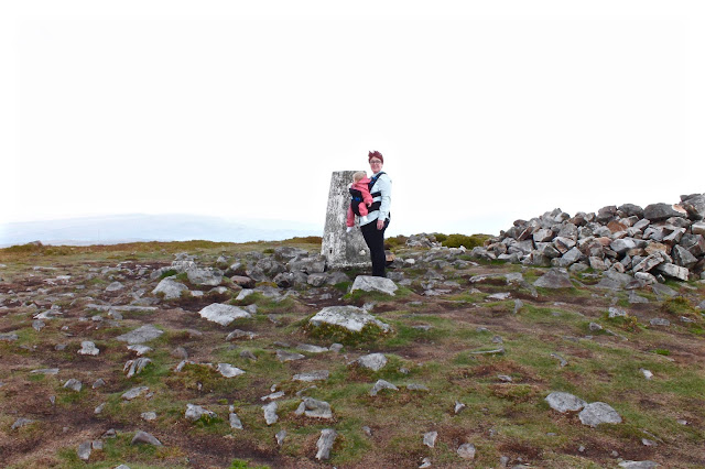 side shot of pao papoose three in one baby carrier next to mountain marker up the blorenge in wales