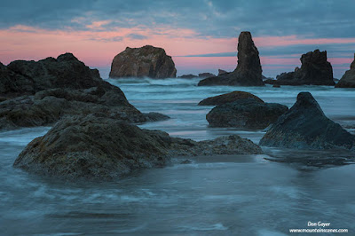 Pink skies after sunset behind sea stacks at Bandon Beach along the Oregon coast, USA.