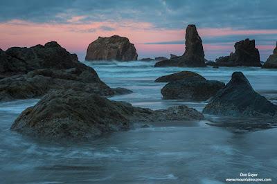 Pink skies after sunset behind sea stacks at Bandon Beach along the Oregon coast, USA.