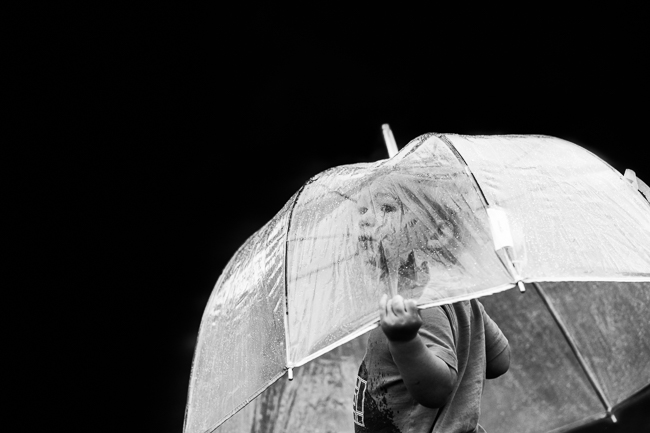Little Boy standing under a clear umbrella in the rain black and white photography