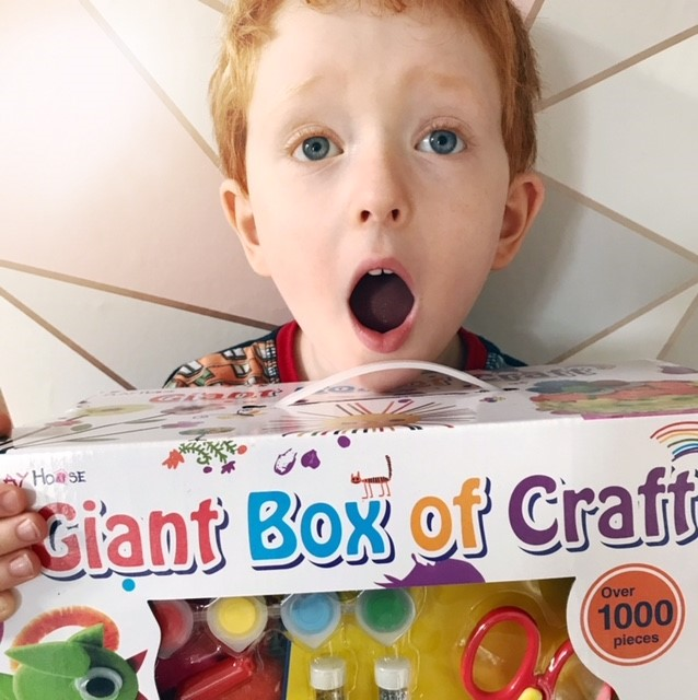 I little boy holding a box of craft supplies looking shocked