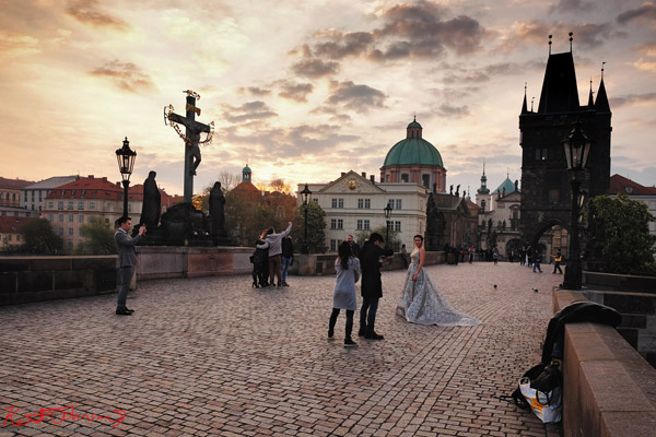 A dawn bridal photoshoot on the Charles Bridge in Spring Prague by Travel and Lifestyle Photographer Kent Johnson.