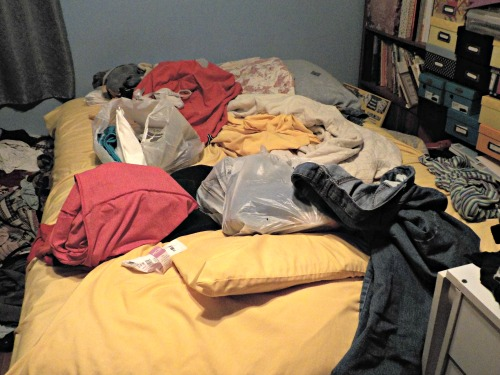 An unmade bed covered with dirty clothes.