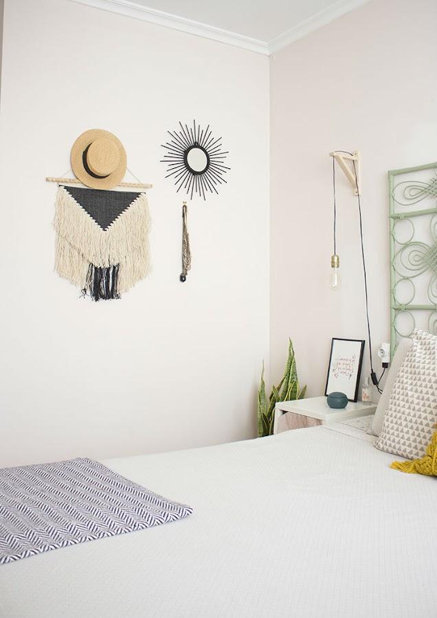 dormitorio con tapiz, espejo sol