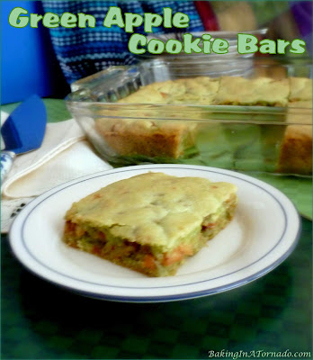 Sweet and tart come together in these Green Apple Cookie Bars featuring a brown sugar apple layer as well as cinnamon and toffee chips. | Recipe developed by www.BakingInATornado.com | #recipe #dessert