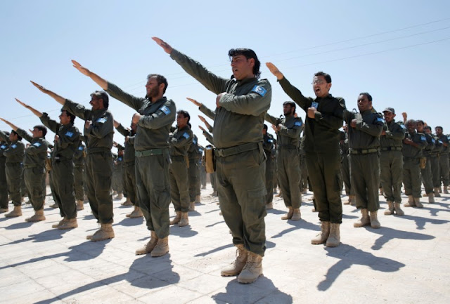 FILE PHOTO: Graduates of a U.S.-trained police force, which expects to be deployed in Raqqa, salute during a graduation ceremony near Ain Issa village, north of Raqqa, Syria, June 17, 2017. REUTERS/Goran Tomasevic/File Photo