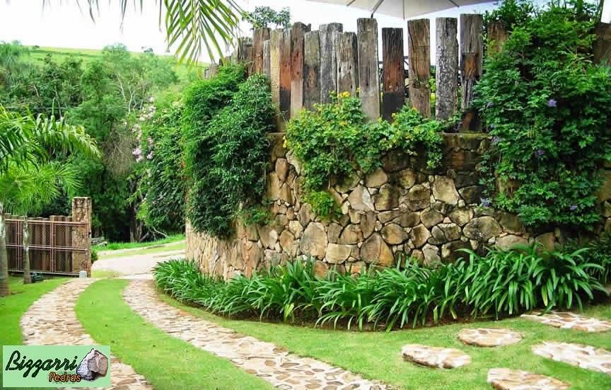 Construção do muro de arrimo com pedra com o para-peito em dormentes de madeira com o caminho de pedra integrando com a execução do paisagismo.