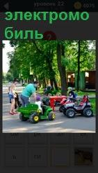 В детском парке дети катаются на электромобилях с родителями в солнечный прекрасный день