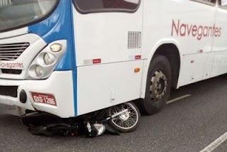 Moto vai parar embaixo de ônibus após colisão e motociclista é socorrido