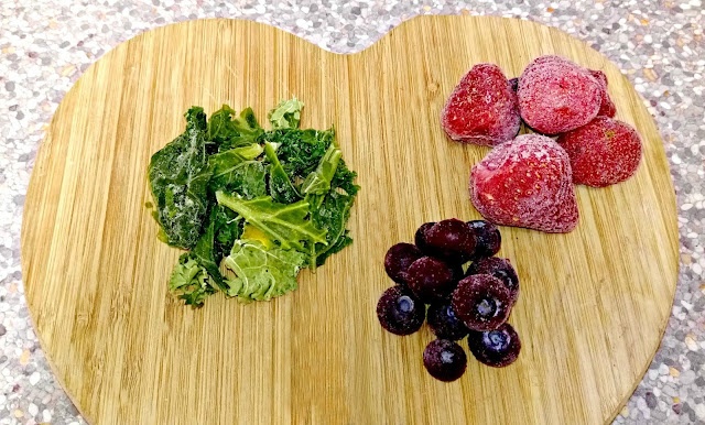 Frozen berries and kale arranged on a wooden chopping board.