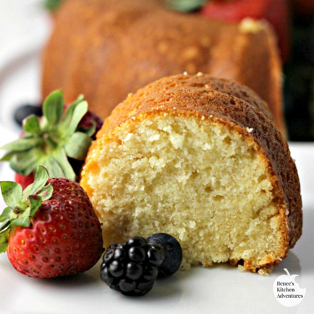 Slice of Buttermilk Pound Cake on white plate with berries in foreground, whole cake in background