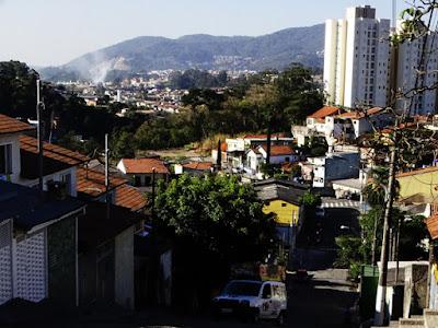 Vista da rua Praia dos Estaleiros com duas das seis torres do Bosque Jaraguá (à direita) e com o que parece ser parte da Pedreira Juruaçu, em Perus (no fundo da foto, à esquerda)