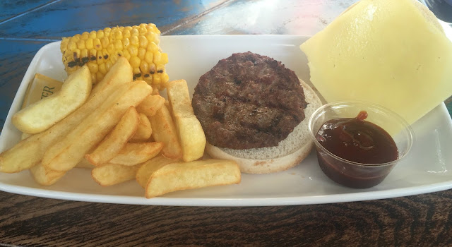 Children cheese burger and chips with corn on the cob
