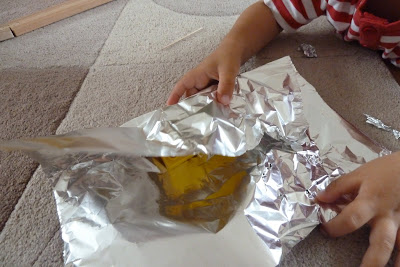 Child wrapping toys in tin foil