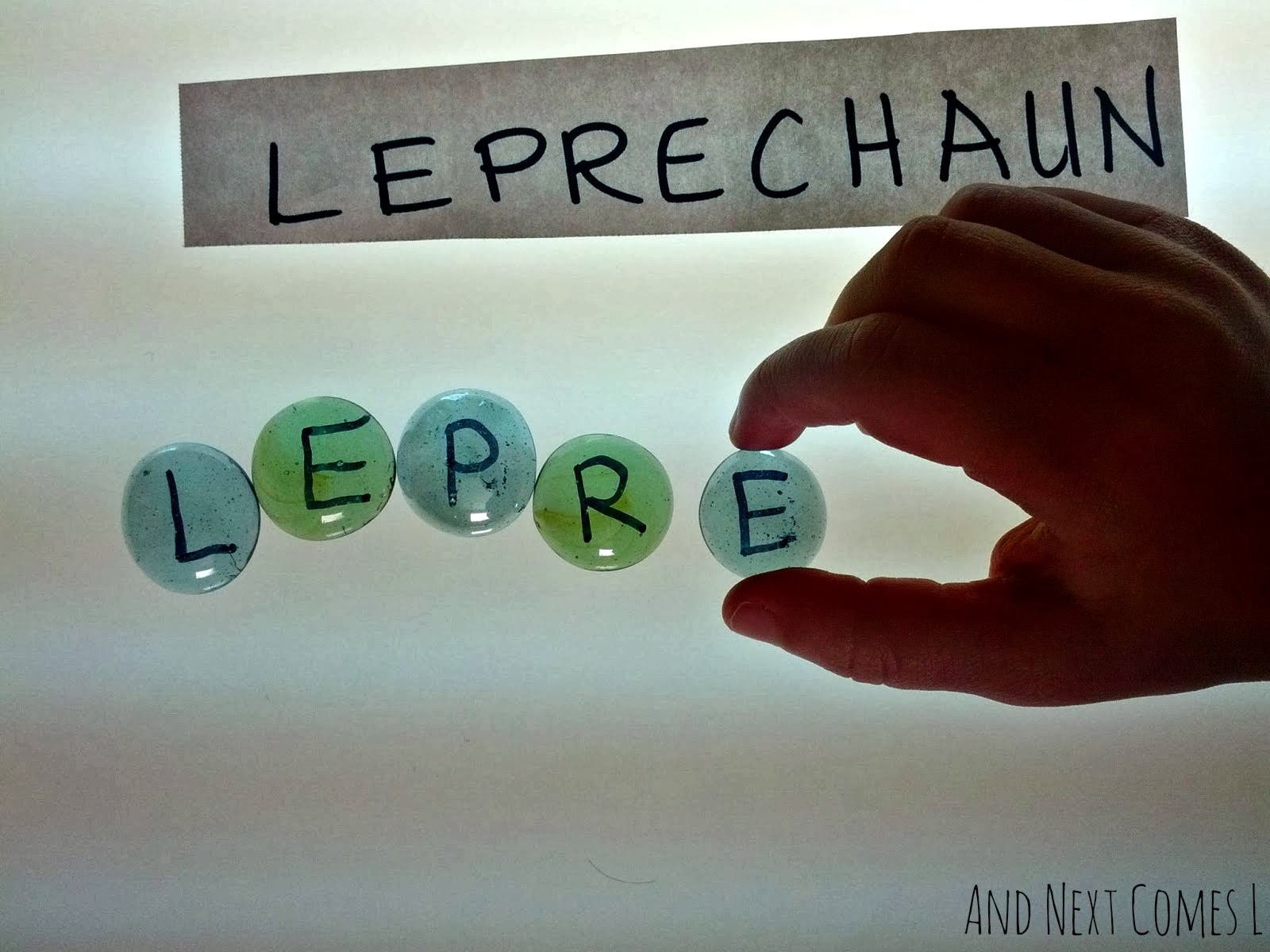 Spelling with homemade alphabet stones on the light table from And Next Comes L
