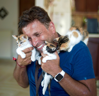 man holding three tortie and white kittens