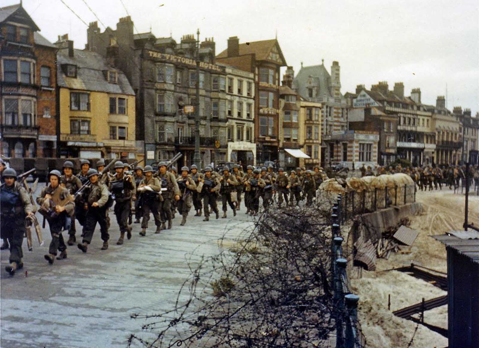 American troops march through the streets of a British port town on their way to the docks where they will be loaded into landing craft for the D-Day assault in June of 1944.