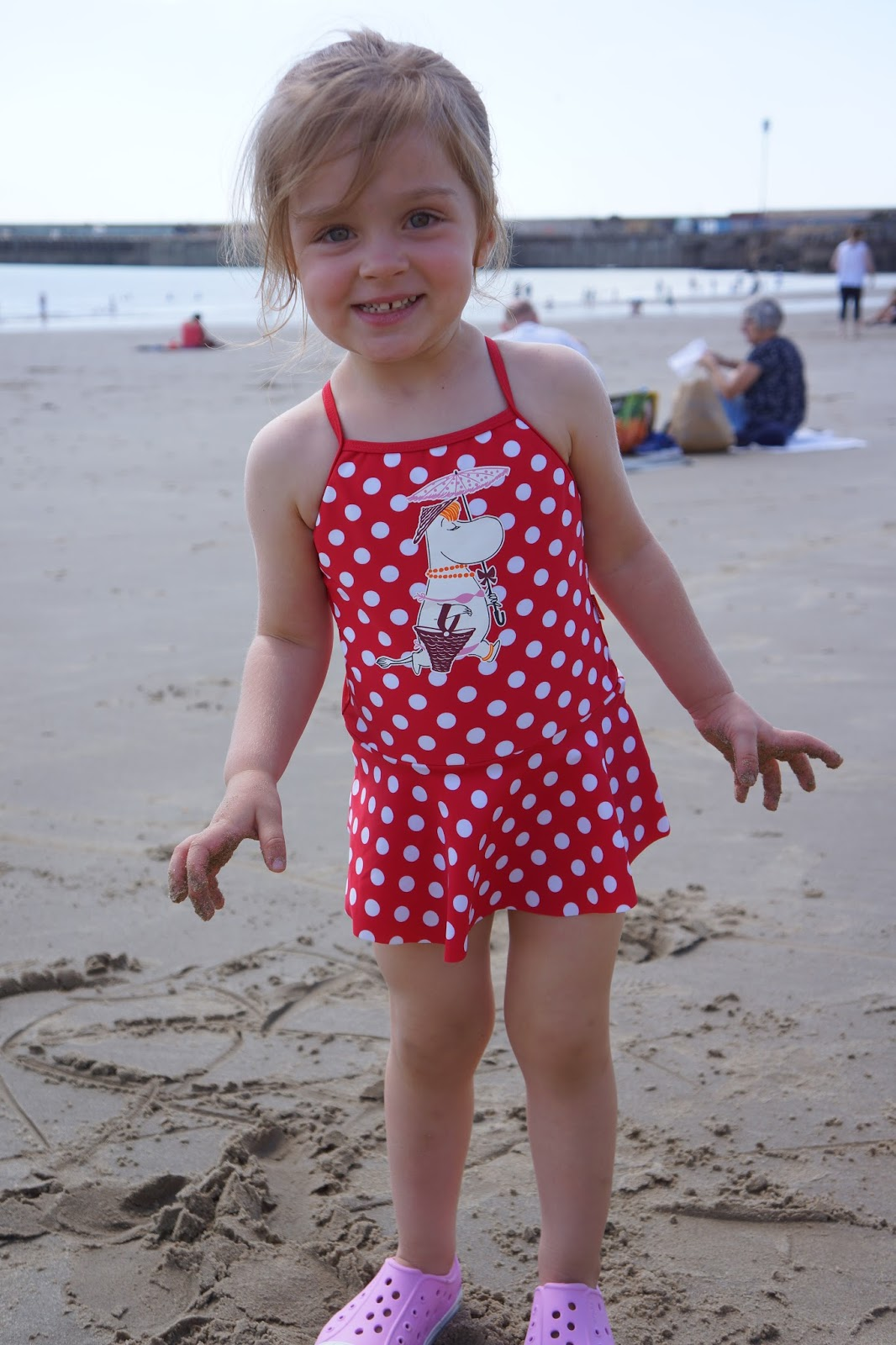 toddler girl wearing a red polkadot Moomin swimsuit