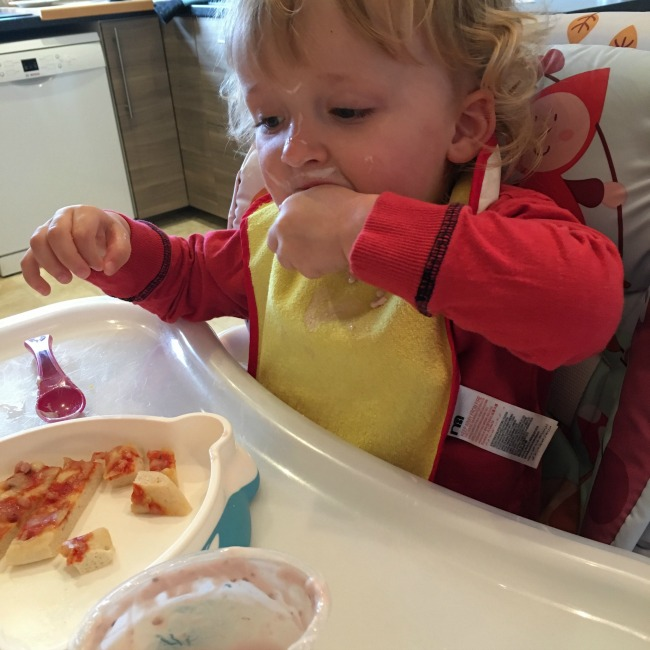 toddler eating with yoghurt on face