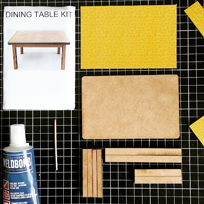Pieces for a one-twelfth scale dining table kit, including glue, toothpick and patterned paper for the tabletop, all laid out on a cutting mat.