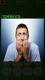 у мужчины тревожный взгляд и руки сложены около рта