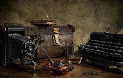 Στη φωτογραφία εικονίζονται μία γραφομηχανή, δερμάτινη τσάντα, φωτογραφική μηχανή παλαιού τύπου, ακουμπισμένα σε ξύλινο τραπέζι. Τη φωτογραφία συμπληρώνουν ξύλινη πίπα μέσα σε τασάκι, κέρματα και ένα ποτήρι με ουίσκυ.