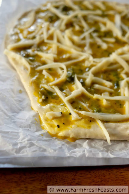 Image of Easy Chile Relleno Pizza ready to bake, with egg mixture spilling onto parchment paper