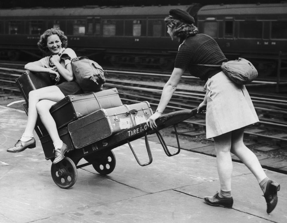 Two holidaymakers amuse themselves with a porters trolley whilst waiting for their train at euston station in 1939