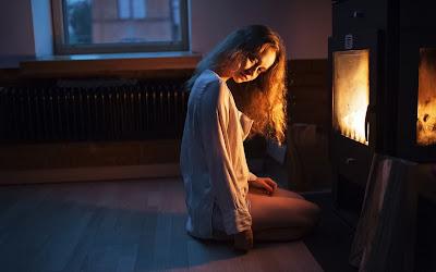 Chica en pijama sentada en la cama delante de la estufa
