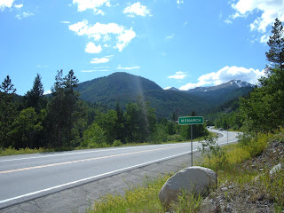 A sunny day with clouds in the sky along the Monarch highway sign.