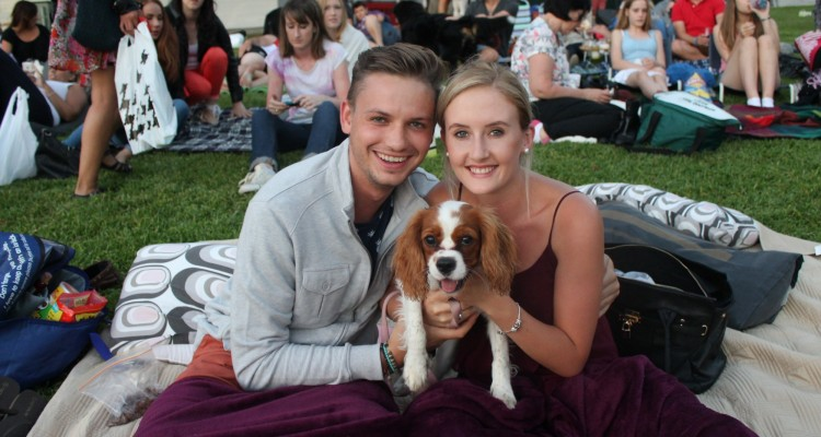Young couple with their Cavalier King Charles Spaniel at a Moonlight Cinema doggie night