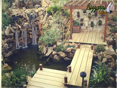 Construção do lago de carpas com a ponte de madeira com pranchas de madeira de Garapeira com o pergolado de madeira, a parede de pedra rústica no fundo e no jardim o paisagismo com pedras.